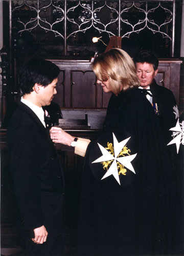 Derwin Mak receiving the decoration of a Serving Brother of the Order of St. John from Hilary Weston, Lt. Governor of Ontario, June 1999.